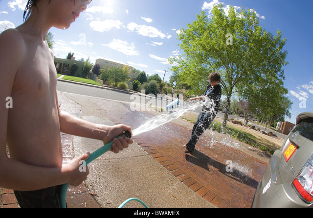Two children having a water fight on a hot summer day, being told to wash car, but  playing instead. USA - Stock Image
