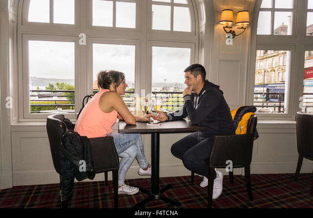 Young couple holding hands having serious conversation at pub in Argyll Hotel, Dunoon, Scotland.   ©Myrleen - Stock-Bilder