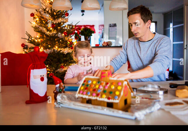 Father and daughter with gingerbread house at table during Christmas - Stock-Bilder