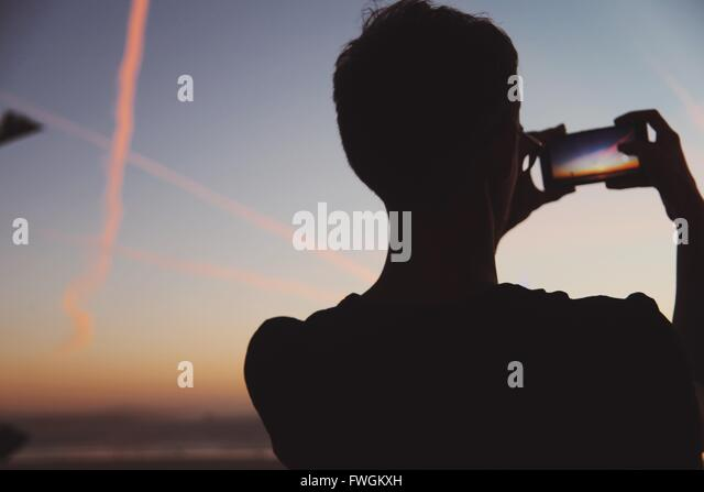 Rear View Of Man Photographing Nature At Dusk - Stock Image