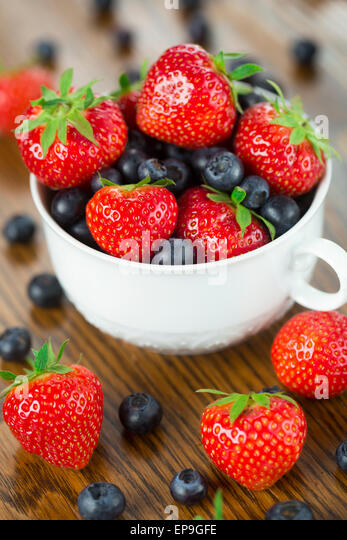 Bowl of strawberries and blueberries on a wooden table - Stock Image