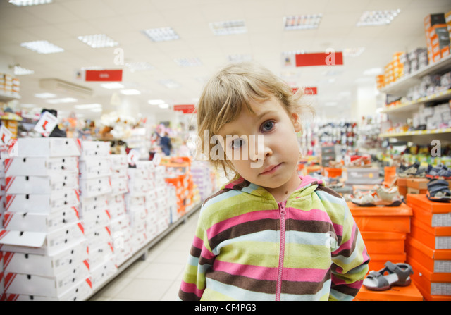 little girl in supermarket alone, chooses in department footwear - Stock Image