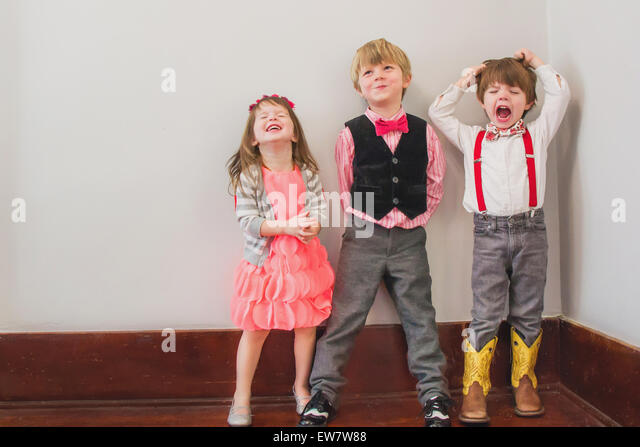 Three children in fancy dress messing about - Stock Image