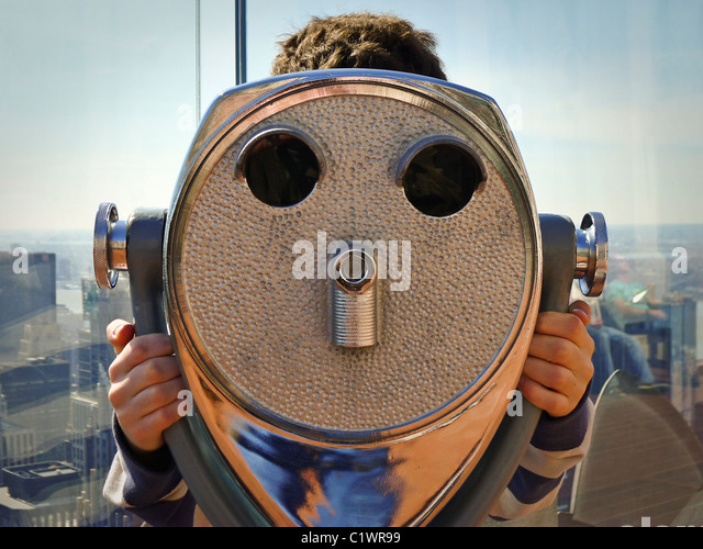 Tourist looking through sightseeing viewer. - Stock Image