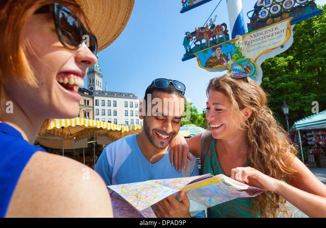 Friends looking at map in Munich Viktualienmarkt, Munich, Germany - Stock Image