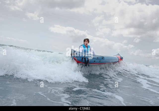 Businessman pushing canoe in ocean - Stock Image