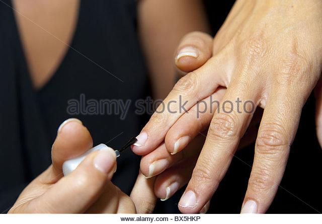 Beautician applying nail polish - Stock Image