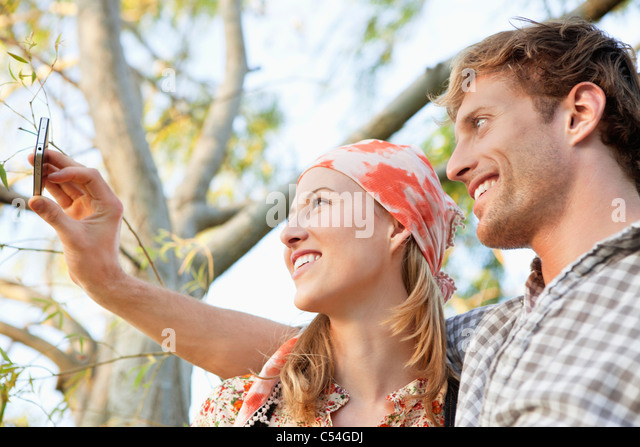 Young couple taking a picture of themselves with a mobile phone - Stock Image