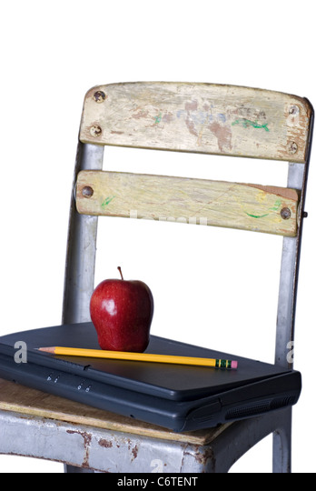 An old school chair holding a closed laptop with a red apple and sharp pencil on the seat, against a 255 white background. - Stock Image
