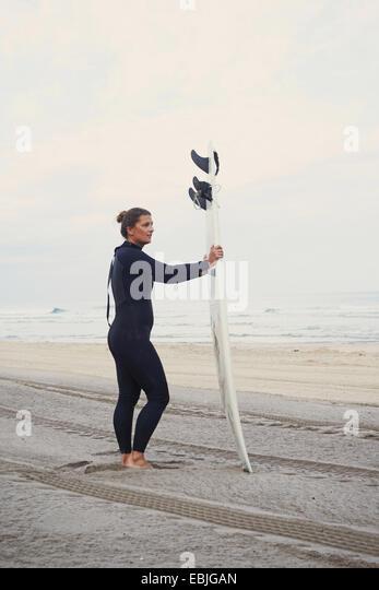 Surfer with surfboard on beach, Lacanau, France - Stock-Bilder