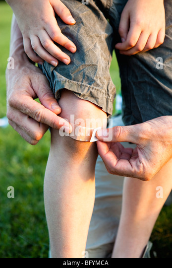 Father Applying Bandage to Knee close-up - Stock Image