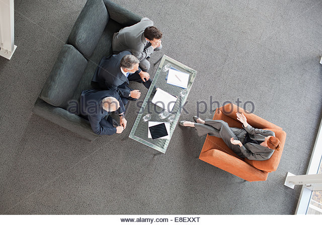 Businesswoman leading meeting with co-workers in lobby - Stock-Bilder