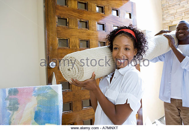 Couple moving house carrying rolled up carpet on shoulders through doorway smiling - Stock-Bilder