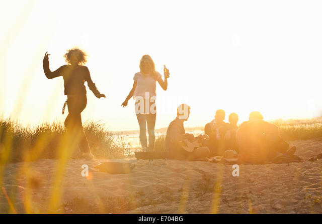 Six adult friends partying at sunset on Bournemouth beach, Dorset, UK - Stock Image