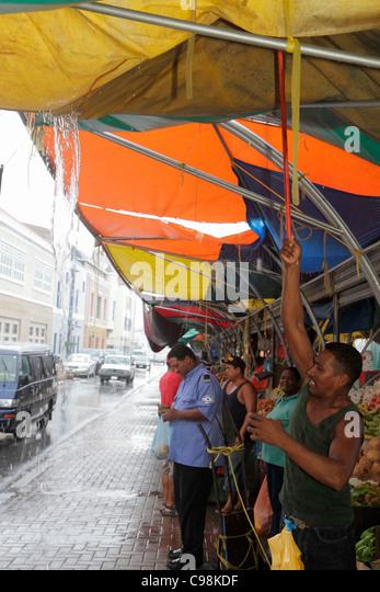 Curaçao Netherlands Antilles Dutch Willemstad Punda Sha Caprileskade Floating Market rain awning wet pavement - Stock Image