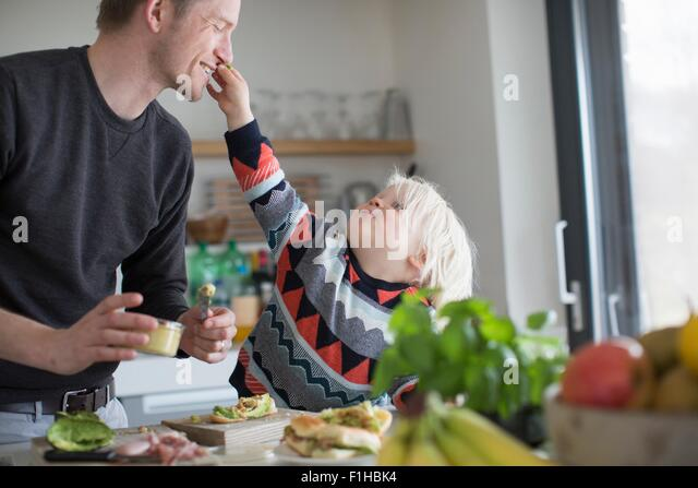 Boy touching father's face in kitchen - Stock Image