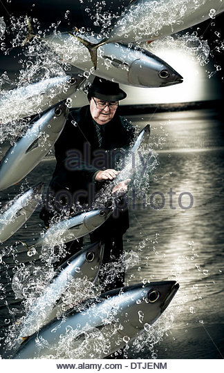 Artistic And Creative Photo Of A School Of Fish Splashing By A Senior Man Trying His Hand A Fishing For A Catch - Stock Image