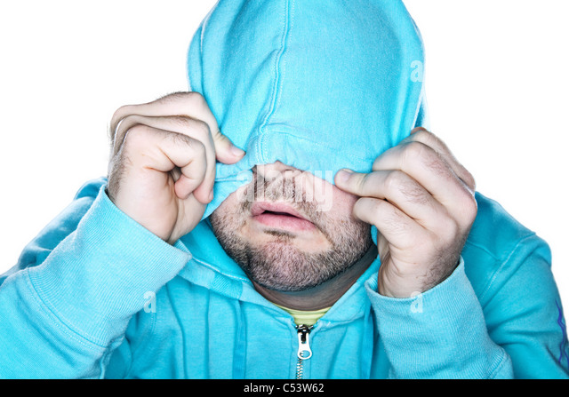 Scruffy man pulling a bright blue hoodie over his face, with a comedic expression. - Stock Image