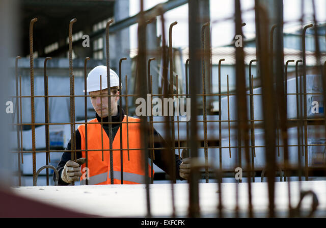 Factory worker choosing wire mesh in concrete reinforcement factory - Stock Image