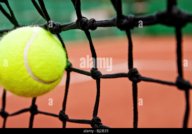 Failure or defeat concept - tennis ball in the net - Stock Image