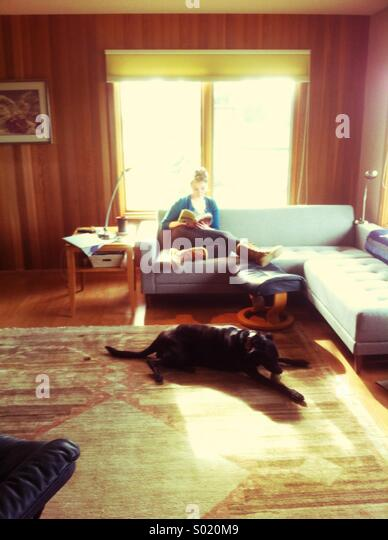 Young woman reading in living room with black dog on carpet - Stock Image