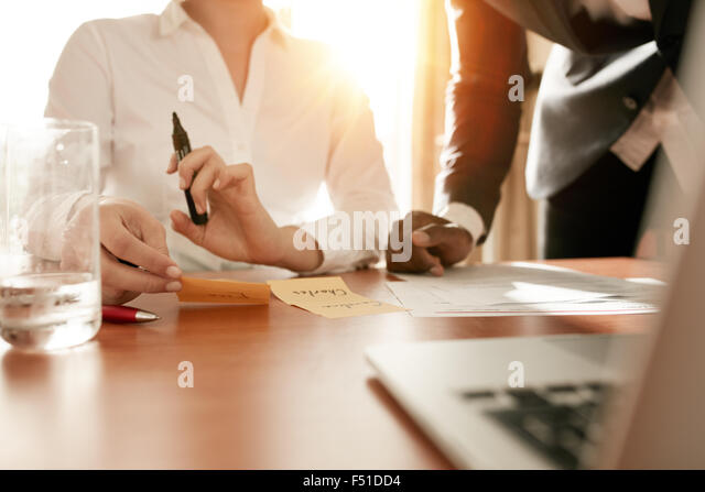 Cropped shot of two businesspeople discussing names written on sticky notes. Business executives doing manpower - Stock Image