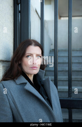 An attractive woman with long dark hair, wearing a formal coat,looks to camera beside a set of railed gates - Stock Image