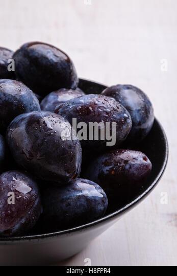 fresh organic tasty plums in black bowl - Stock Image