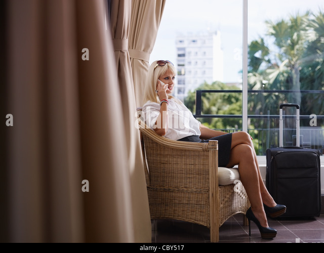 Mid adult caucasian manager speaking on cell phone in hotel room during business trip. Side view, full length, copy - Stock Image