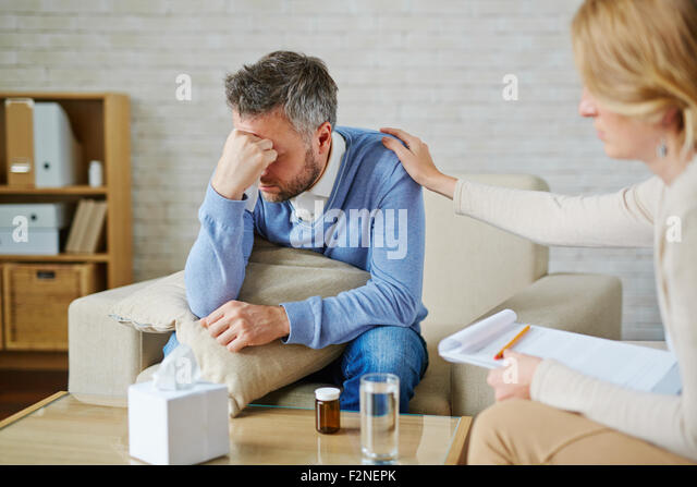 Despaired man with pillow and handkerchief being reassured by his psychologist - Stock Image