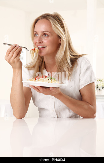 WOMAN EATING PASTA - Stock Image