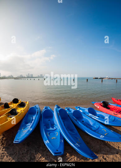 Colorful kayaks line the shore of North Avenue Beach on Lake Michigan, in the Gold Coast district of Chicago, Illinois. - Stock Image