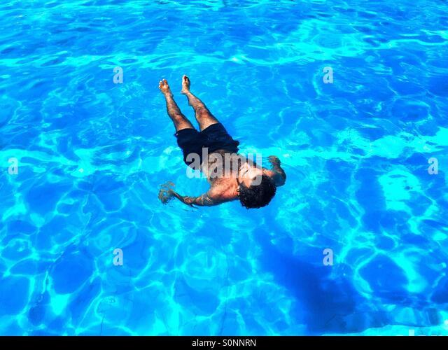 Man chilling in the swimming pool - Stock Image