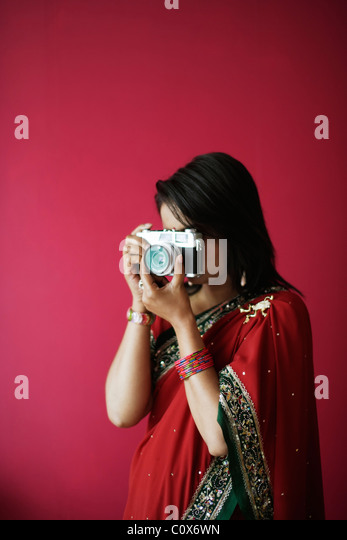 Punjabi woman in red sari takes picture with old film camera - Stock Image