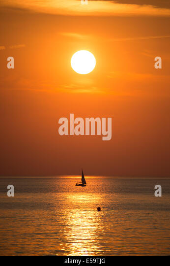 Aberystwyth, Wales, UK. 24th July, 2014. A lone yacht sailing at sunset on Cardigan Bay Aberystwyth on the west - Stock Image