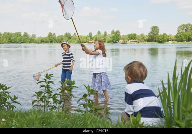 Three friends fishing in the lake, Bavaria, Germany - Stock Image
