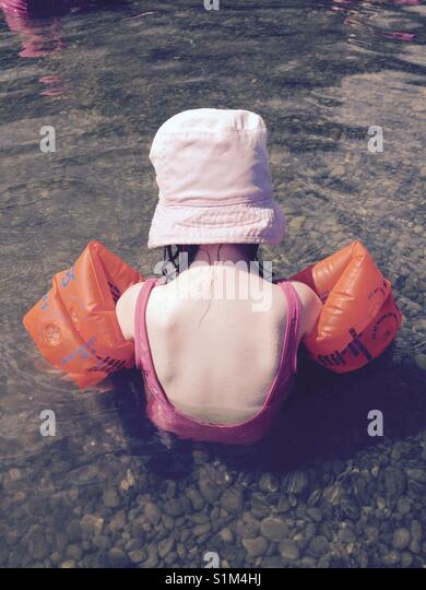 Young girl / toddler goes swimming with sun hat and armbands - Stock Image