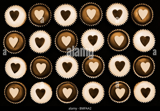 Mini cupcakes decorated with heart shapes. Sepia tone - Stock Image