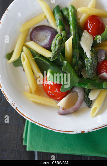 Close up of noodle salad with ruccola, asparagus, parmesan and cherry tomatoes - Stock-Bilder