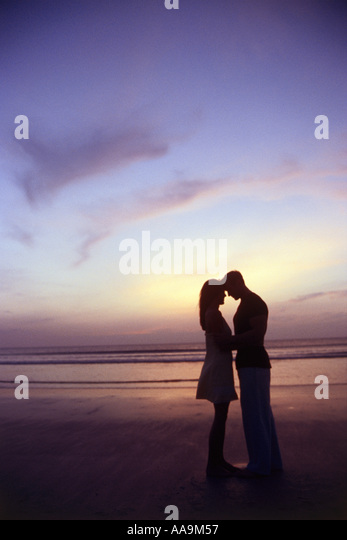 Silhouette of a young couple together at the beach - Stock-Bilder