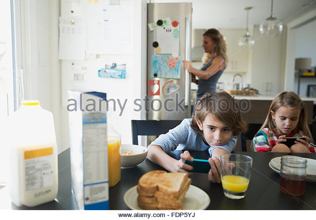 Brother and sister using cell phones breakfast table - Stock Image