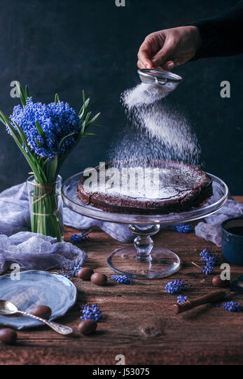 Woman sprinkling powdered sugar on top of Swedish chocolate cake on a cake stand - Stock Image