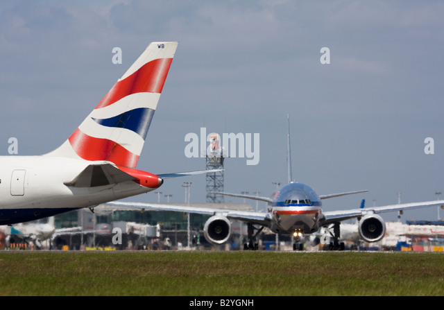 The tail of British Airways plane and American Airlines plane Boeing 777 - London Heathrow, United Kingdom - Stock Image
