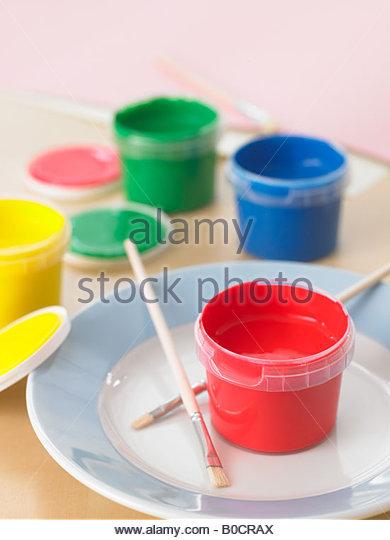 Close-up of watercolor paints and two paintbrushes on a plate - Stock-Bilder