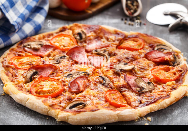 Pizza with tomatoes, ham and mushrooms on a table - Stock Image