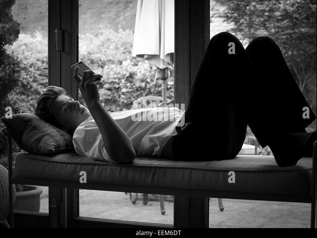Teenage boy relaxing using smart phone - Stock Image