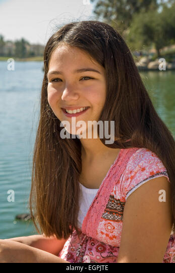 Hispanic-Caucasian teen girl 11-13 year old smiling portrait in park with lake.mixed race, racial mix diversity - Stock-Bilder