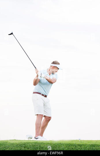 Full-length of mid-adult man swinging golf club against clear sky - Stock Image