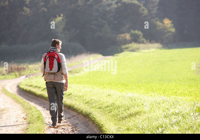 Young man walks in park - Stock Image