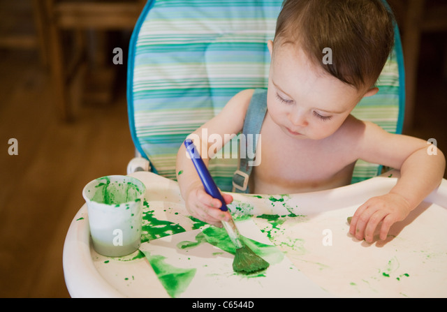 Baby boy sitting in high chair painting picture - Stock Image
